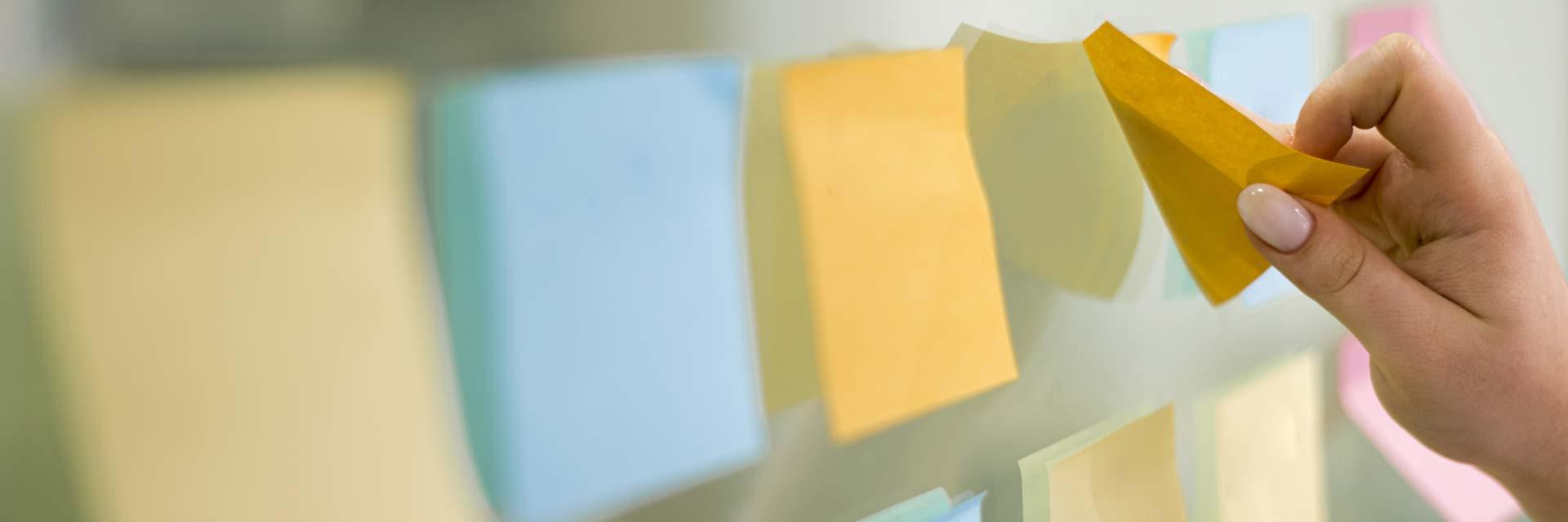 Metod för coachning illustrerat av olikfärgade notislappar på vägg