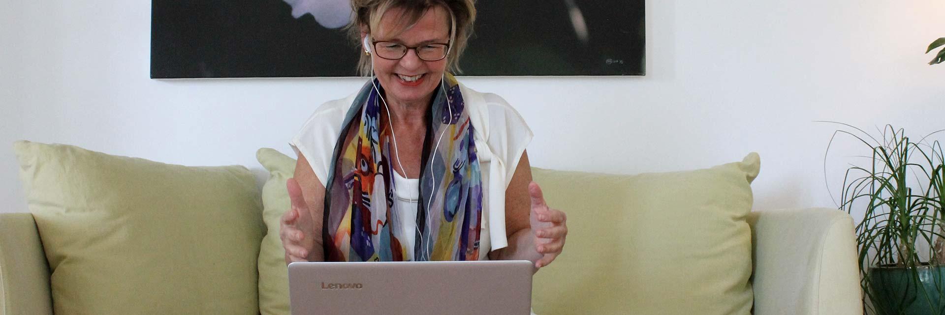 Digital coach på distans, online med dator, säljcoach ledarcoach sittande glad kvinna med fototavla bakom